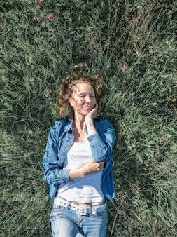 緑の花のフィールドの上に横たわる美しい中年の女性