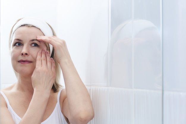 Beautiful middle-aged woman makes self-massage of the face around the eyes in front of a mirror in a bathroom