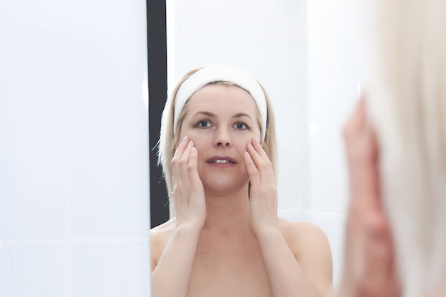 Beautiful middle-aged woman makes self-massage of the face around the eyes in front of a mirror
