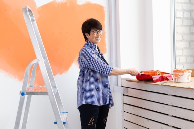 Beautiful middle-aged woman painting wall in her new apartment.