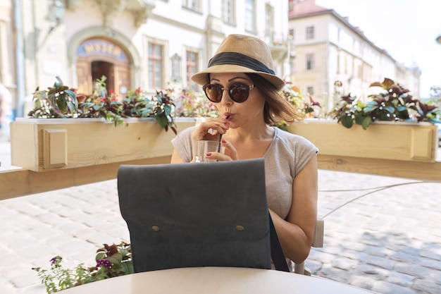 Beautiful middle-aged woman in sunglasses, hat drinking cold drink in summer outdoor cafe, female sitting alone, smiling looking away