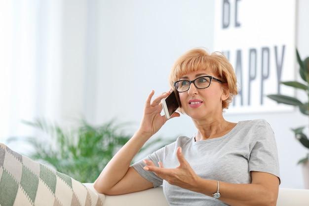 自宅で携帯電話で話している美しい中年女性