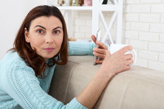 Красивая женщина средних лет с чашкой и смартфоном расслабляется дома.