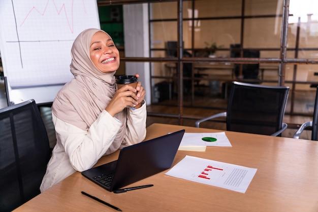 그녀의 사무실에서 일하는 히잡을 쓴 아름다운 중동 사업가