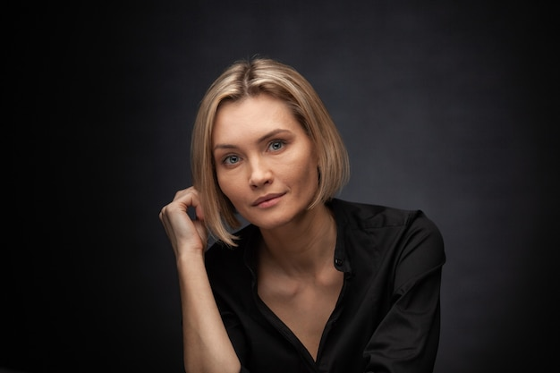 Beautiful middleaged woman on a gray background in a black blouse