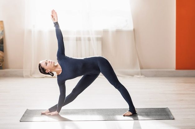A beautiful middleaged woman practicing yoga at home doing extended triangle exercises