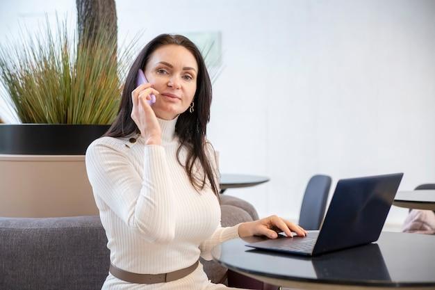Красивая женщина среднего возраста улыбается, разговаривает по телефону на ноутбуке в офисе