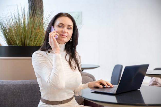Beautiful middleaged woman smiling talking on the phone at laptop in office
