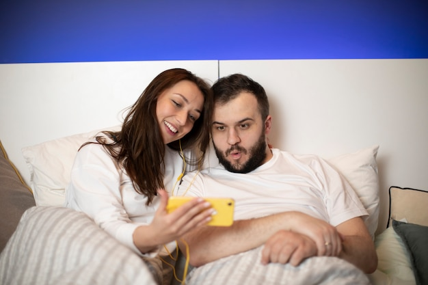 Beautiful millennial couple using mobille phone lying on bed together