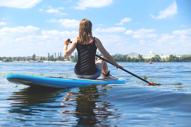 川のsupボード上の美しいミレニアル世代の女性