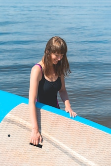 A beautiful millennial woman smiles and holds a bobboard in her hands while standing by the river