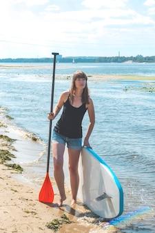 Supボードと川の水たまりを持つ美しいミレニアル世代の女性