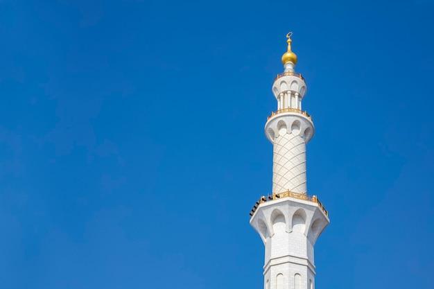 Красивый минарет башни мечети из белого мрамора на фоне голубого неба.