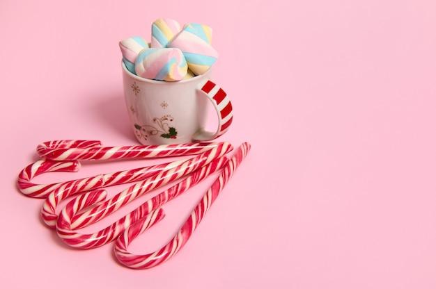 Красивая минималистичная рождественская композиция с горячим шоколадным напитком, украшенная зефиром и полосатыми леденцами, леденцы, изолированные на розовом фоне с копией пространства для рекламы