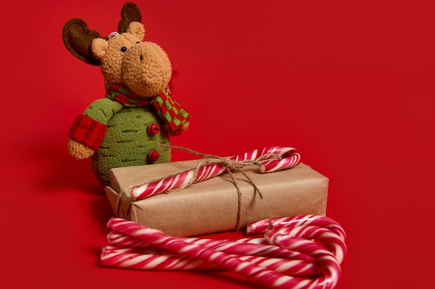 Beautiful minimalist composition of christmas items, gift box in kraft wrapping paper with tied bow, sweet lollipops and deer plush toy on red background with copy space for ad