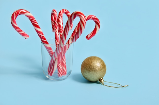 Beautiful minimalist simple composition with christmas lollipops in a transparent glass and golden christmas ball, christmas tree toy on a blue background with copy space for advertising