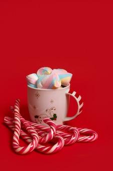 Красивая минималистичная рождественская композиция с горячим шоколадным напитком, украшенная маршмеллоу и полосатыми леденцами на палочке, леденцы, изолированные на красном фоне с копией пространства для рекламы