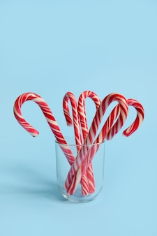 Beautiful minimalistic simple composition with candy canes on a transparent glass on a blue background with copy space for christmas advertisement