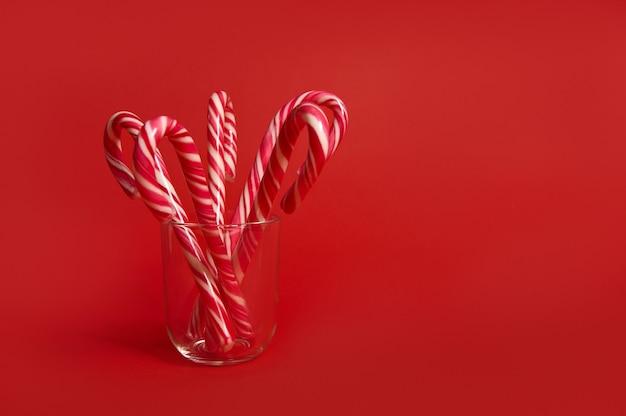 Красивая минималистичная простая композиция с рождественскими леденцами на прозрачном стекле на цветном ярко-красном фоне с копией пространства для рекламы