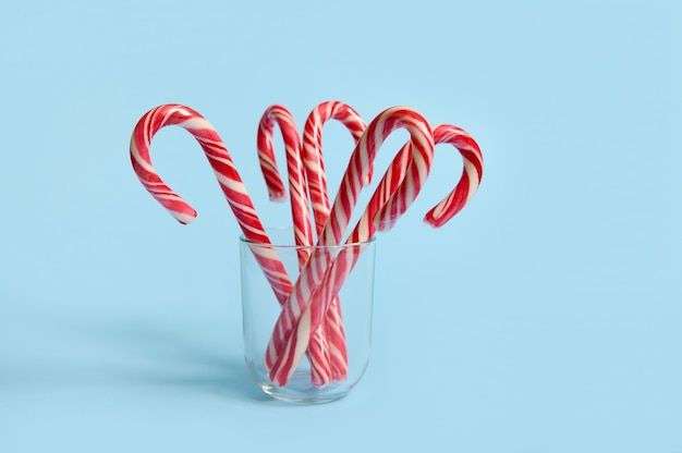 Beautiful minimalistic simple composition with christmas lollipops on transparent glass on blue background with copy space for christmas ad