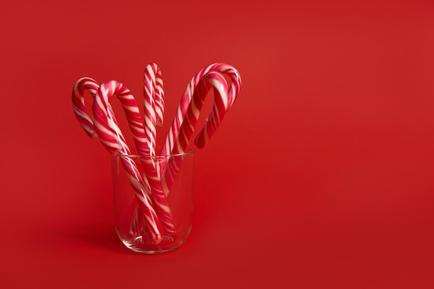 Beautiful minimalistic simple composition with christmas lollipops on transparent glass on colored bright red background with copy space for advertising