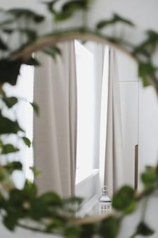 家の内部の観葉植物によって飾られた美しい鏡
