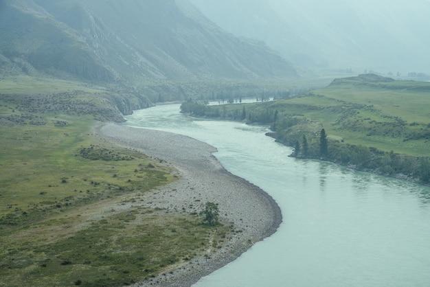 広い山川のある美しい霧深い山の風景。霧の中に大きな山川がある濃い緑色の暗い風景。雨天時の大きな山々に囲まれた大河の暗い雰囲気。