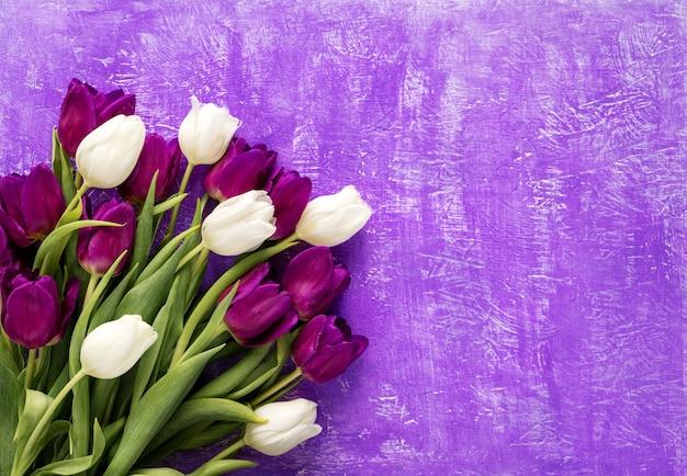 Красивый микс букет из фиолетовых и белых тюльпанов на фиолетовом столе. весенние цветы тюльпаны стол с копией пространства