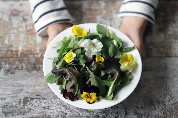 白い皿の上の花とサラダの美しいミックス。ダイエットのコンセプトです。女の子のための栄養。健康なビーガンフード。