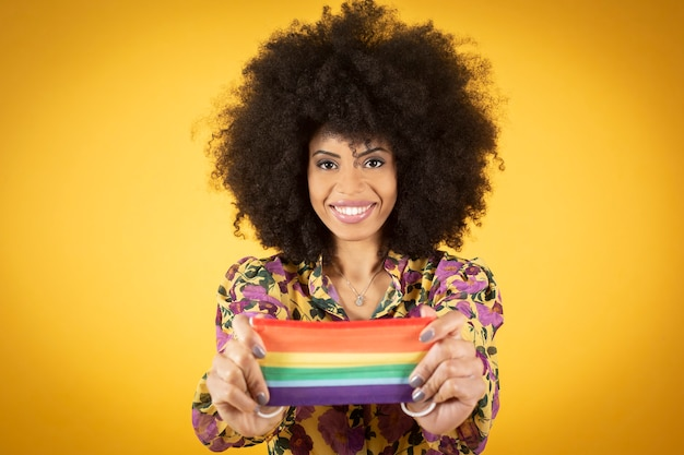 Beautiful mixed afro american hipster with protective mask yellow background