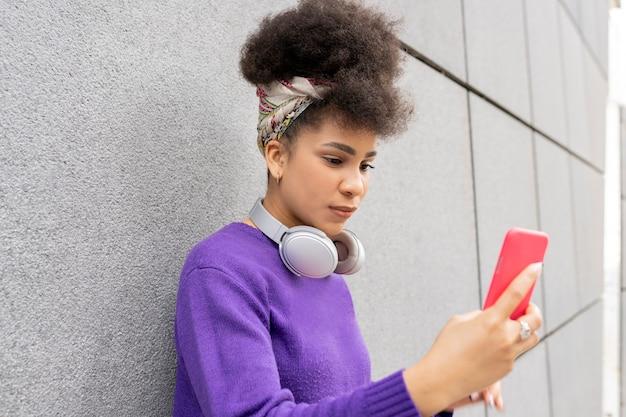 通りに携帯電話で、カジュアルな服を着た美しい混合アフロ女性