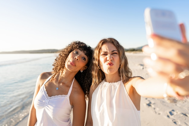 Beautiful mixed race female couple making faces doing self portrait on beach