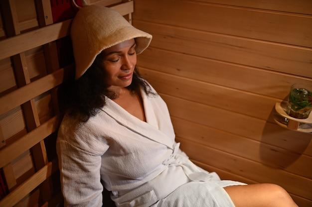 적외선 사우나에서 쉬고 있는 아름다운 혼혈 여성. 확대. 스파 트리트먼트, 대체 뷰티 테라피.