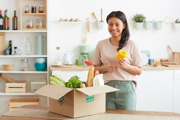 Красивая женщина смешанной расы улыбается, наслаждаясь службой доставки еды, стоя возле коробки с овощами на кухне