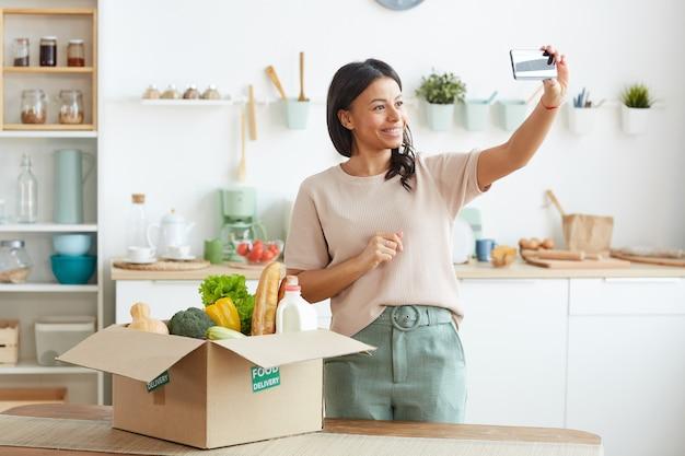 Красивая женщина смешанной расы улыбается во время записи видео о доставке еды через смартфон
