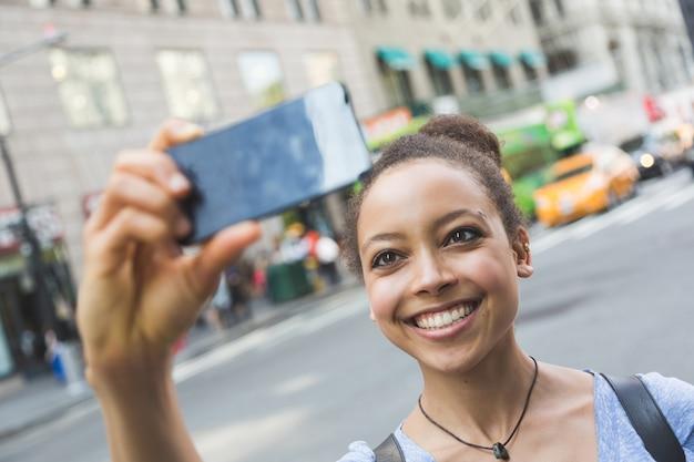 Beautiful mixed race woman taking selfie in new york
