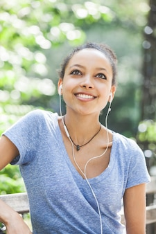 Beautiful mixed-race young woman listening music with earphones at park