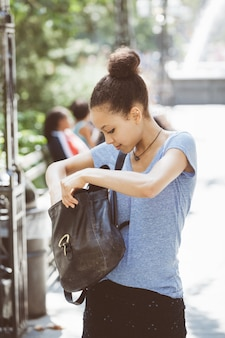 Beautiful mixed-race young woman looking inside her bag