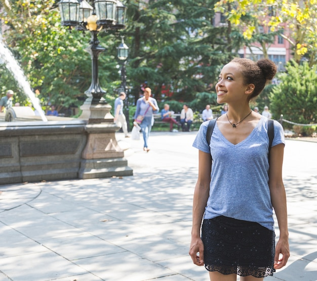Beautiful mixed-race young woman at park, smiling portrait