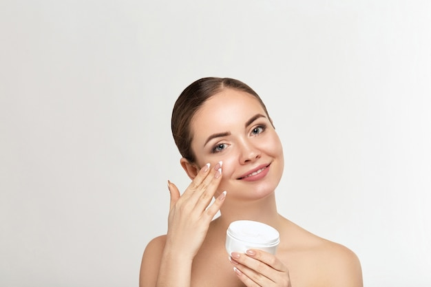 Beautiful model applying cosmetic cream treatment on her face on white background