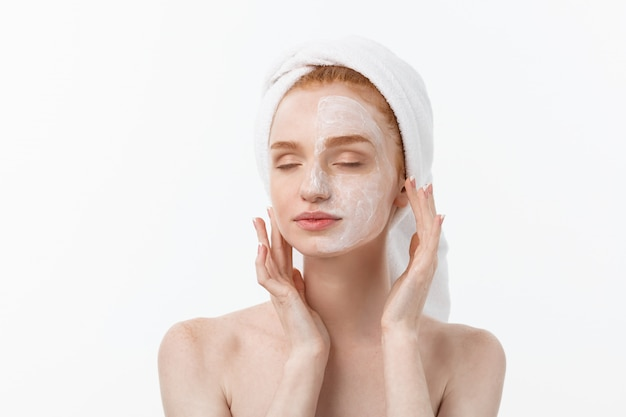 Beautiful model applying cosmetic cream treatment on her face on white.