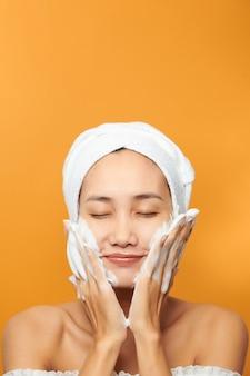 Красивая модель, применяя косметический крем на лице на оранжевом фоне