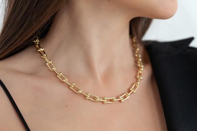 Красивая модель брюнетка в современной золотой металлической цепочке ожерелья