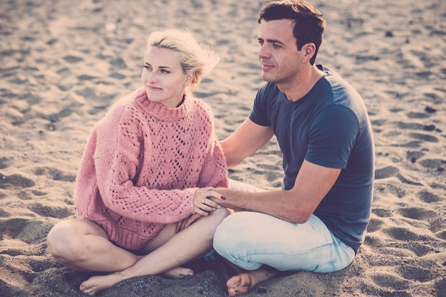 Красивая модельная пара кавказских юная леди и мужчина остаются в любви, обниматься и сидеть на пляже. светлые и черные волосы в отношениях на свежем воздухе. отпуск и образ жизни