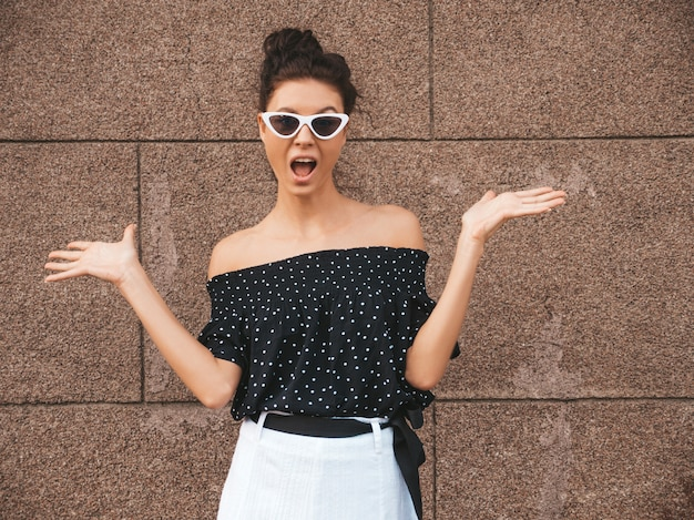 Beautiful model dressed in elegant summer clothes.sexy carefree girl posing in the street near wall.trendy modern businesswoman in sunglasses.displaying something on both flat hands for similar choice