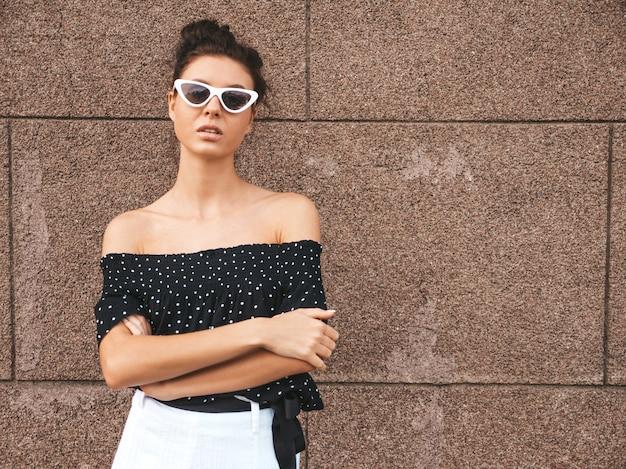 エレガントな夏の服に身を包んだ美しいモデル。壁の近くの通りでポーズをとってセクシーな屈託のない少女。楽しいサングラスで流行のモダンな実業家