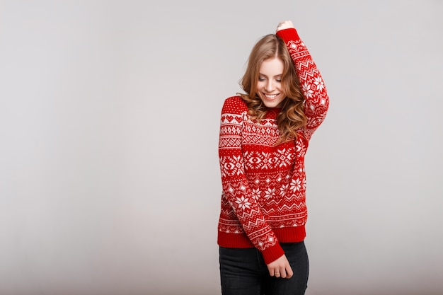 Beautiful model girl in a fashionable red knitted sweets on a gray background