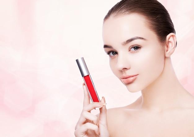 ピンクのボケ味の背景に赤いペンキのはねと口紅のチューブを保持している美しいモデルの女の子