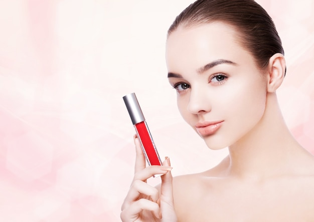 Beautiful model girl holding lipstick tube with red paint splashes on pink bokeh background