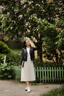 Красивая модель девушка в белой миди-юбке и черной кожаной куртке позирует возле цветущей сирени молодая брюнетка женщина в весеннем наряде позирует на открытом воздухе